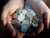 Монетки владением руки Деньги сбережений или концепция пожертвования Стоковые Фото