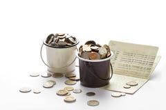 Монетки в ведрах и банковская книжка на предъявителя сберегательного счета, банк книги на белизне Стоковое фото RF