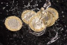 Монетки в воде брызгают на черной предпосылке Стоковое Изображение