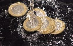 Монетки в воде брызгают на черной предпосылке Стоковая Фотография