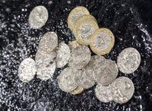 Монетки в воде брызгают на черной предпосылке Стоковые Изображения