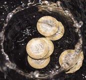 Монетки в воде брызгают на черной предпосылке Стоковые Фото
