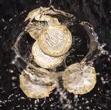 Монетки в воде брызгают на черной предпосылке Стоковые Фотографии RF