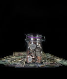 Монетки в опарнике каменщика на валюте кровати Стоковые Фото