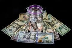 Монетки в опарнике каменщика на валюте кровати Стоковая Фотография