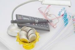 Монетки в подносе золота с постаментом на обработке документов с лампой Стоковое фото RF