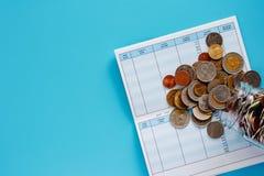 Монетки в стеклянных опарнике и снаружи, тайских деньгах валюты на планировании стоковое фото
