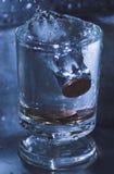 Монетки в стеклянной воде Стоковое Фото
