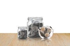Монетки в стеклянном опарнике на деревянном поле, сбережения чеканят - концепция денег сбережений концепции вклада и интереса, ра Стоковые Изображения RF