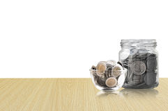 Монетки в стеклянном опарнике на деревянном поле, сбережения чеканят - концепция денег сбережений концепции вклада и интереса, ра Стоковая Фотография RF