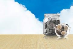 Монетки в стеклянном опарнике на деревянном поле, сбережения чеканят - концепция денег сбережений концепции вклада и интереса, ра Стоковое фото RF