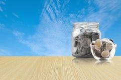 Монетки в стеклянном опарнике на деревянном поле, сбережения чеканят - концепция денег сбережений концепции вклада и интереса, ра Стоковые Изображения