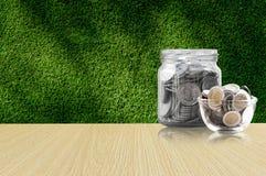 Монетки в стеклянном опарнике на деревянном поле, сбережения чеканят - концепция денег сбережений концепции вклада и интереса, ра Стоковая Фотография