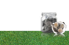 Монетки в стеклянном опарнике на поле травы, сбережения чеканят - концепция денег сбережений концепции вклада и интереса, растущи Стоковая Фотография