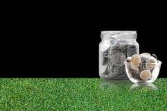 Монетки в стеклянном опарнике на поле травы, сбережения чеканят - концепция денег сбережений концепции вклада и интереса, растущи Стоковое Фото