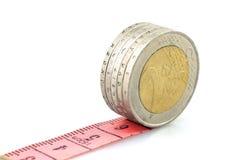 Монетки евро бежать на красном правителе Стоковое Изображение