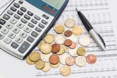 Монетки евро, ручка и часть калькулятора на таблице данных Стоковые Фотографии RF