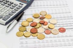 Монетки евро, ручка и часть калькулятора на таблице данных Стоковое фото RF