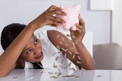 Монетки женщины падая от Piggybank стоковая фотография rf