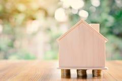 Монетки и деревянный дом на предпосылке bokeh дерева таблицы Стоковое фото RF