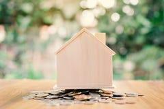 Монетки и деревянный дом на предпосылке bokeh дерева таблицы Стоковая Фотография