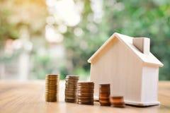 Монетки и деревянный дом на предпосылке bokeh дерева таблицы Стоковые Изображения RF