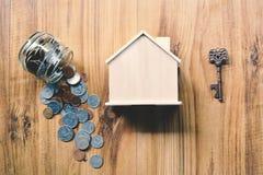 Монетки и деревянный дом на таблице Стоковое фото RF