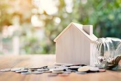 Монетки и деревянный дом на таблице Стоковые Изображения