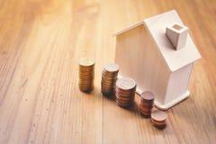 Монетки и деревянный дом на таблице Стоковая Фотография RF