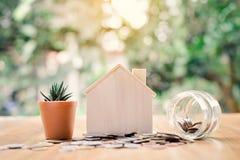 Монетки и деревянный дом с кактусом на предпосылке bokeh дерева таблицы Стоковые Фото