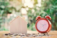 Монетки и деревянный дом с красным будильником на предпосылке bokeh дерева таблицы Стоковые Изображения