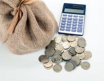 Монетки и калькулятор русского рубля с сумкой денег на белой таблице стоковые фото