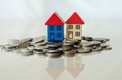 Монетки и дома стоя на ем стоковое изображение rf