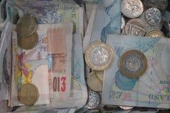 Монетки и примечания фунта стоковые фото