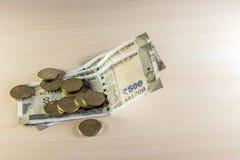 Монетки и 500 рупий примечаний на деревянном столе Стоковые Фото