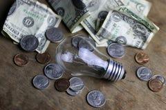 Монетки и скомканная нить лампы вольфрама денег стоковое изображение