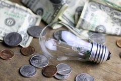 Монетки и скомканная нить лампы вольфрама денег стоковая фотография