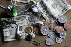 Монетки и скомканная нить лампы вольфрама денег стоковые фото