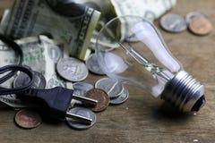 Монетки и скомканная нить лампы вольфрама денег стоковое фото