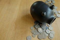 Монетки и черная копилка на деревянной таблице Стоковое фото RF