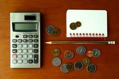 Монетки, калькулятор, карандаш и тетрадь Стоковые Фотографии RF
