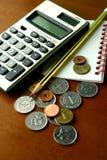 Монетки, калькулятор, карандаш и тетрадь Стоковые Изображения