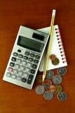 Монетки, калькулятор, карандаш и тетрадь Стоковое Изображение