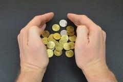 Монетки между руками человека на черной предпосылке Стоковые Фотографии RF