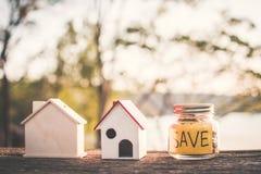 Монетки на стеклянном опарнике с домом слова и модели спасения на таблице в предпосылке bokeh природы Стоковые Изображения
