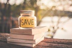 Монетки на стеклянном опарнике с словом спасения и книге на таблице в предпосылке bokeh природы Стоковое Фото