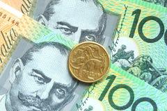 Монетки одного доллара австралийские на 100 предпосылках банкноты Стоковые Изображения