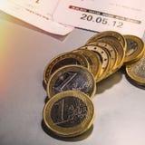 Монетки одно евро и проверки лежат на таблице Стоковые Изображения RF