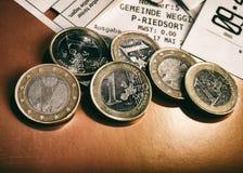 Монетки одно евро и проверки лежат на таблице Стоковые Фотографии RF