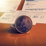 Монетки одно евро и проверки лежат на таблице Стоковая Фотография RF